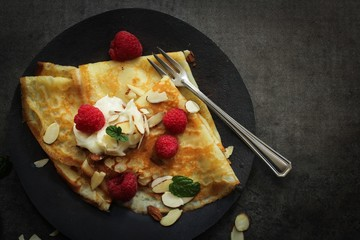 French Breakfast Crepes served with Raspberries  on dark moody background,Top Down view