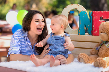 Adorable infant baby on first birthday with mother, balloons and stuffed animal at park