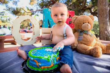 Funny cute adorable expression on baby eating first birthday cake with hands during his party