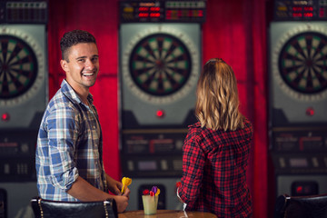 Portrait of beautiful young couple playing darts