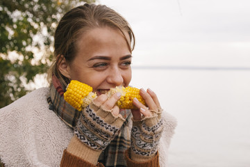 Portrait of girl eating boiled corn in the nature