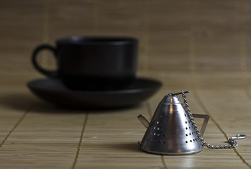 Tea strainer on the background of the Cup