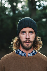 Portrait of a bearded man standing in the forest looking at camera