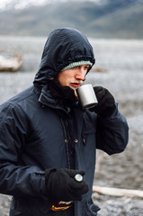 Young man drinking fine whisky on a cold day in the chilean Patagonia