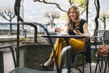 Young beautiful blonde woman sitting at cafe