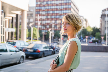 Portrait of a beautiful blonde woman standing on the street looking away