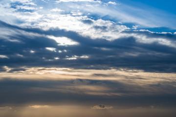 Himmel mit Sonnenlicht und Wolken am Abend, blaue und orange-gelbe Farben