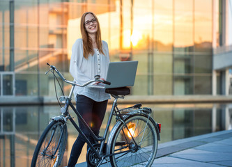 a young charming woman standing with her bicycle near the river somewhere in the city and working with a laptop; warm golden sunlight is reflected from a glass building across the river