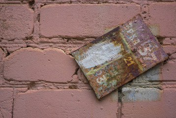 The dirty tablet on a pink brick wall