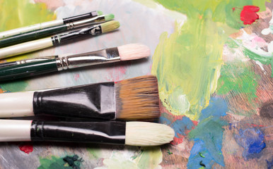 Artist paint brushes and oil paint  on wooden artistic palette background. Brush paint artistic. Tools for creative work. Back to school. Paintings Art Concept. Selective focus. Copy space. Top view.