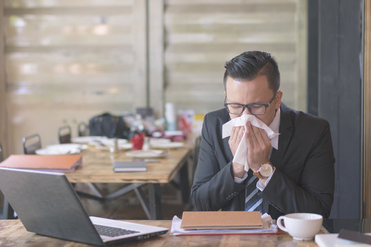 Sick and tired. Frustrated young man massaging his nose and keeping eyes closed while sitting at his working place in off