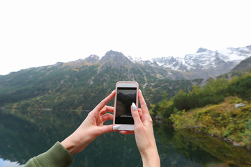 The girl takes a picture on the background of a mountain lake