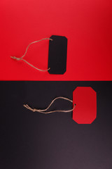 Black tag on a red background and a red tag on a black background.