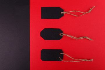 Black tags on a bright red background. The black background is empty.
