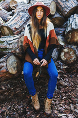 Hipster woman sitting in front of a stack of trunks.