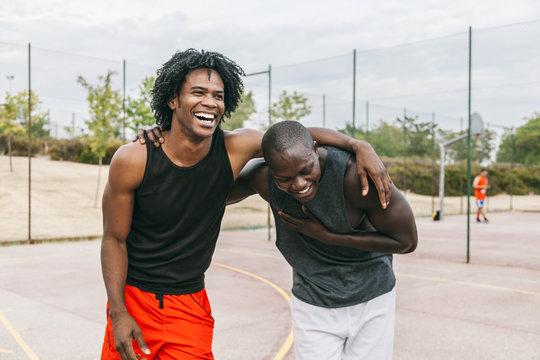 Two Black Friends Having Fun in a Basketball Street Court