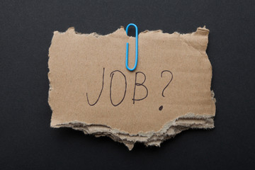 "The word ""Job?"" on a piece of cardboard box on a black background."