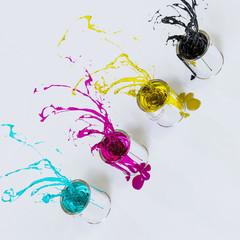 Fontänen aus den Druckfarben CMYK spritzen aus vier Eimern in den Raum