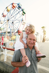 Father and Daughter near Ferris Wheel and Carnival