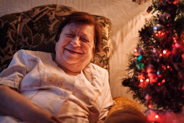 Portrait of old woman smiling looking at camera near Christmas tree