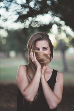 woman is playing with her hair in a park