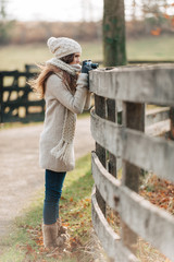 A young girl taking photos of animals at a farm