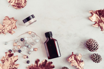 Fall beauty products and accessories with rose gold leaves on white marble table from above. Copy space