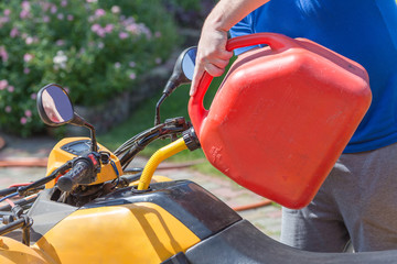 Caucasian man in sport protective goggles holds red canister and pours gasoline into ATV's quadbike tank. Refueling process. Maintenance and service