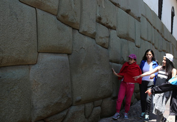 Tourists visit an Inca wall at a street in down town Cuzco