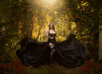 The dark queen of elves walks in the magical garden. A creative image, an unusual black dress. Artistic toning.