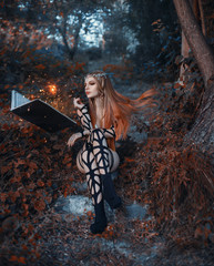 The Dark Elf casts a spell from a magic book. A creative image, an unusual black dress. Artistic toning