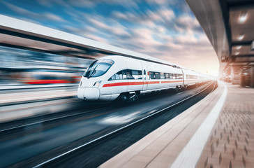 White modern high speed train in motion on railway station at sunset. Train on railroad track with motion blur effect in Europe. Railway platform. Industrial landscape. Railway tourism. Vintage style