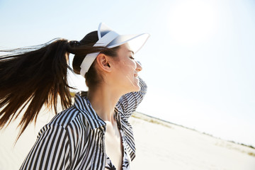 A girl walking in a black and white stripes shirt and a visor hat around a beach enjoying the sun