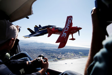 Photographers take pictures as Team Oracle aerobatics pilot Tucker and members of the U.S. Navy Blue Angels flight demonstration squadron fly over San Francisco Bay ahead of Fleet Week in San Francisco