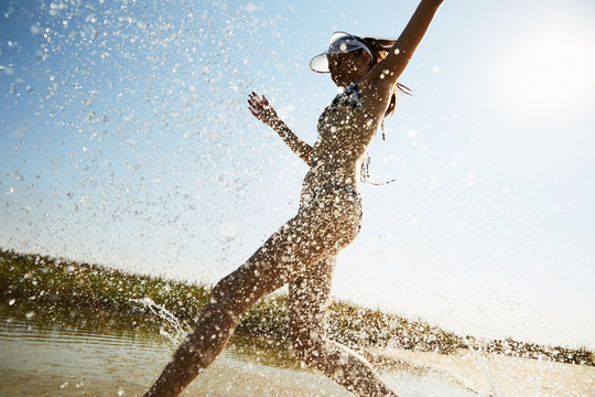 A girl running into the water at the beach with drops flying around