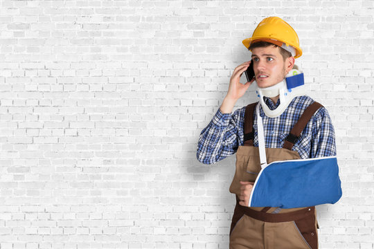 Handyman With Fractured Hand Calling On Mobile Phone