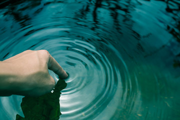 The hands dipped in blue water until the waves.