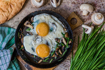 Fried eggs with mushrooms and jusai (allium ramosum). Breakfast in azian style, top view
