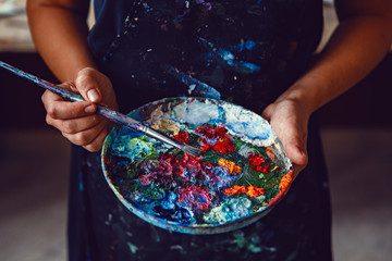 Hands of female artist holding messy dirty palette  with different paints and paintbrush in art studio. Lifestyle and hobby concept Wall mural