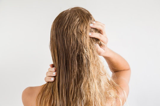 Woman touching her wet blonde hair after shower on the gray background. Before and after hair brushing with comb. Cares about a healthy and clean hair. Beauty salon concept.