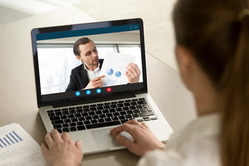 Young businessman shows financial report via video call on laptop screen. Project manager presenting successful investment profit stats to female business partner. Finance success concept. Close up.