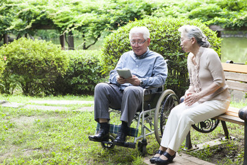 An old couple is using a tablet