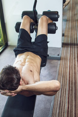 Young handsome muscular man without t-shirt exercising in the gym. Decline bench abdominal crunches target the rectus abdominis, or abdominal muscles.