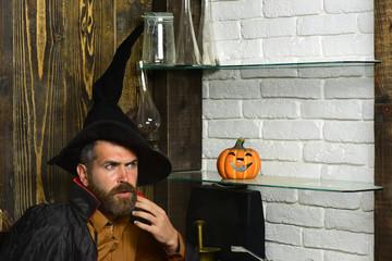 Halloween man wizard sitting in black witch hat with pumkin