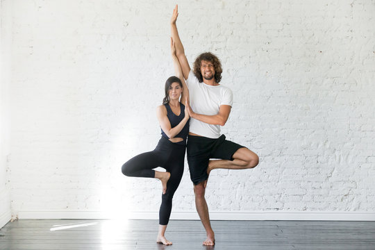 Couple of young sporty people practicing yoga lesson with partner, smiling man and woman standing in Vrksasana exercise, Tree pose, working out, indoor full length, studio. Wellbeing, wellness concept