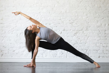 Young woman practicing yoga, stretching in Utthita parsvakonasana exercise, Extended Side Angle pose, working out, wearing sportswear, gray tank top, black pants, indoor full length, studio background Wall mural