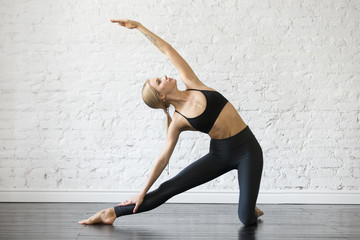 Young attractive woman practicing yoga, stretching in Gate exercise, Parighasana pose, working out, wearing sportswear, black top and pants, indoor full length, studio background