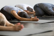 Group of young sporty people practicing yoga lesson with instructor, sitting in Balasana exercise, Child pose, friends working out in club, indoor close up image, studio. Wellbeing, wellness concept