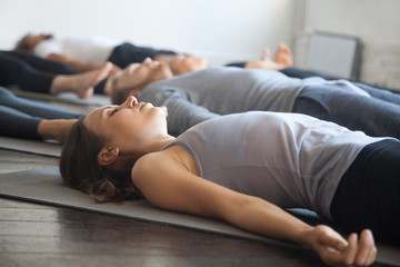 Group of young sporty people practicing yoga lesson with instructor in gym, lying in Dead Body exercise, doing Savasana, Corpse pose, friends relaxing after working out in sport club, studio image Wall mural