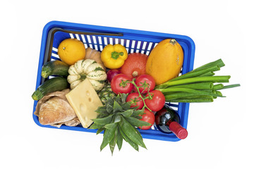 Top view on shopping basket filled with different vegetables and groceries isolated on white background.